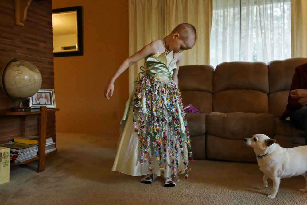 Description of . In this Friday Nov. 2, 2012 photo, Mykayla Comstock, 7, one of Oregon's youngest medical marijuana patients, admires her dress while her dog, Chase, looks on, in Gladstone, Ore. Mykayla's mother says she gives her daughter marijuana pills to combat the effects of chemotherapy, but her father, who lives in North Dakota, worries about the effects of the drug on her brain development. Mykayla was diagnosed with leukemia last spring. (AP Photo/The Oregonian, Beth Nakamura)