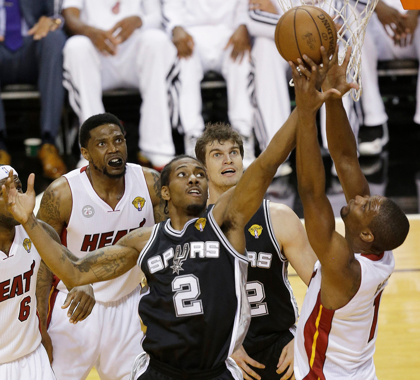. San Antonio Spurs\' Kawhi Leonard (2), and Tiago Splitter (22) of Brazil, and Miami Heat center Chris Bosh (1) vie for a rebound during the first  half of Game 2 of the NBA Finals basketball game, Sunday, June 9, 2013 in Miami.  (AP Photo/Wilfredo Lee)