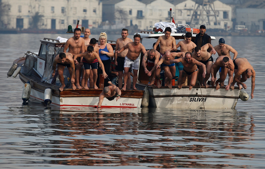 . Swimmers jump into the water to race to retrieve a wooden cross which was thrown into the waters by Ecumenical Patriarch Bartholomew I during a ceremony to bless the water at the Golden Horn in Istanbul, Wednesday, Jan. 6, 2016. The traditional ceremony marks the Epithany in Istanbul when Bartholomew I or an Orthodox priest throws a simple wooden cross into the water and swimmers race to be the first to retrieve it. (AP Photo/Emrah Gurel)