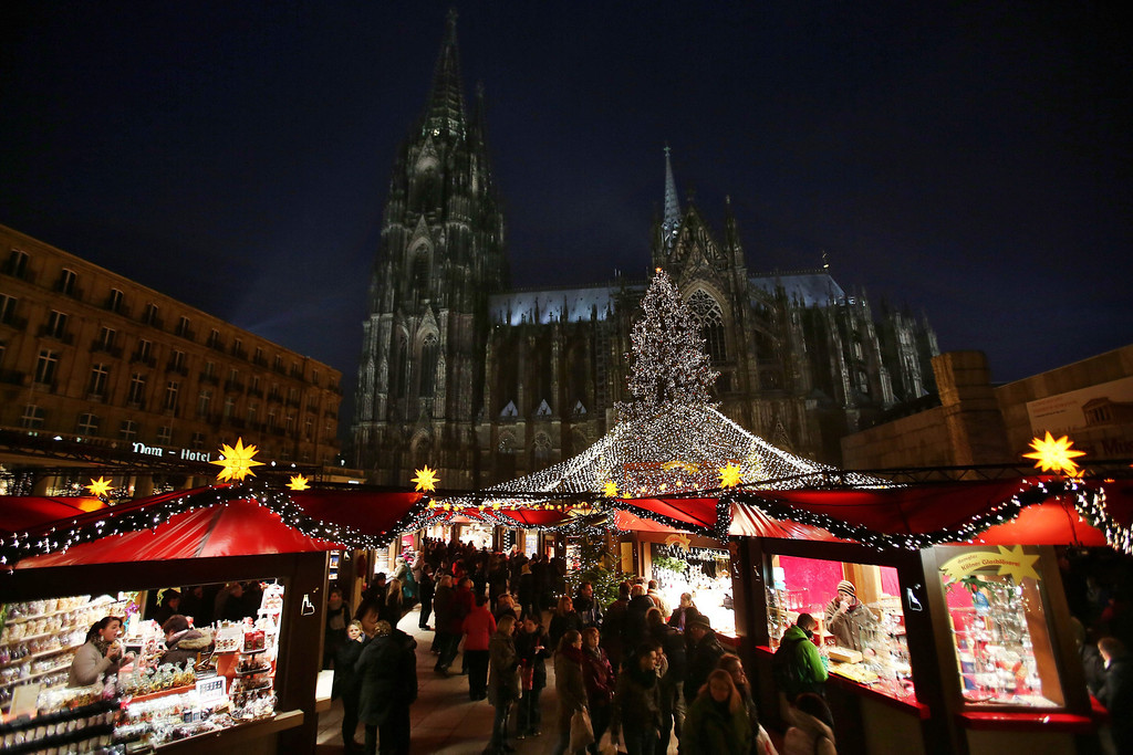 . Visitors walk past stands at the Christmas market in Cologne, Germany, 26 November 2013. In the background is the Cologne Cathedral.  EPA/Oliver Berg