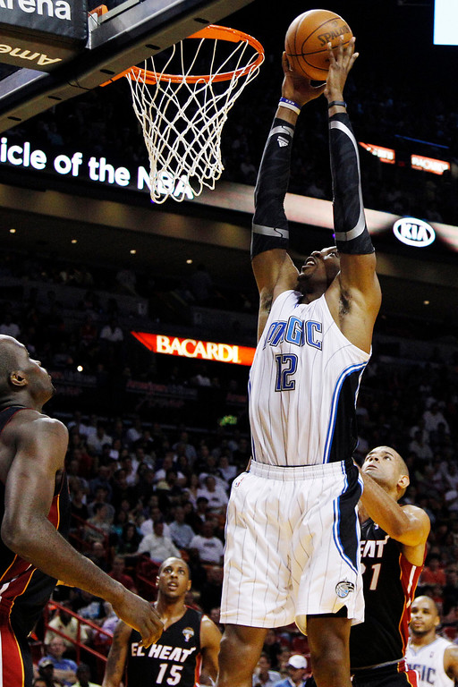 . Orlando Magic\'s Dwight Howard (12) shoots as Miami Heat\'s Joel Anthony (50), Shane Battier (31) and Mario Chalmers (15) watch during the first half of an NBA basketball game, Sunday, March 18, 2012, in Miami. (AP Photo/Lynne Sladky)