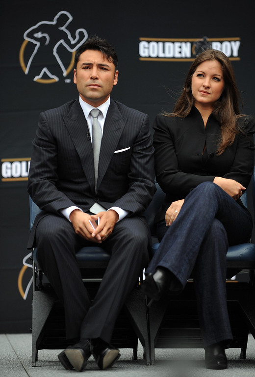 ". Oscar De La Hoya and his wife Millie Corretjer listen to Los Angeles Mayor Antonio Villaraigosa (out of frame) after De La Hoya announced his retirement from boxing at a press conference in Los Angeles on April 14, 2009. The 10-time boxing world champion, ""Golden Boy\"" De la Hoya\'s last bout was back in December when Filipino Manny Pacquiao easily stopped him in the eighth round.   (GABRIEL BOUYS/AFP/Getty Images)"