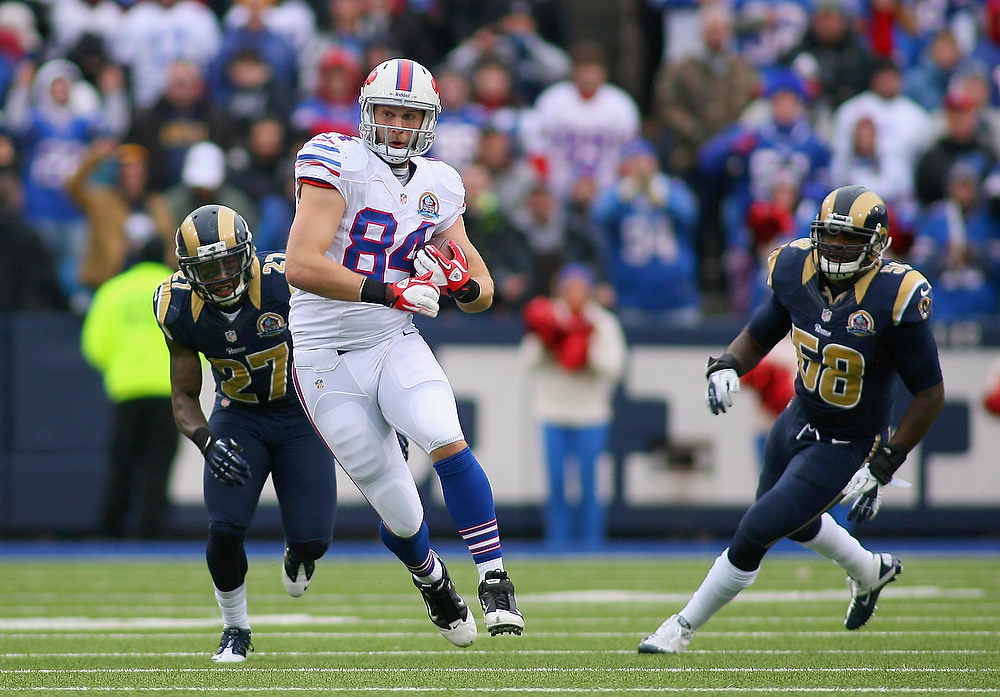 . Scott Chandler #84 of the Buffalo Bills runsa after a catch against Quintin Mikell #27 and Jo-Lonn Dunbar #58 of the St. Louis Rams at Ralph Wilson Stadium on December 9, 2012 in Orchard Park, New York. (Photo by Rick Stewart/Getty Images)