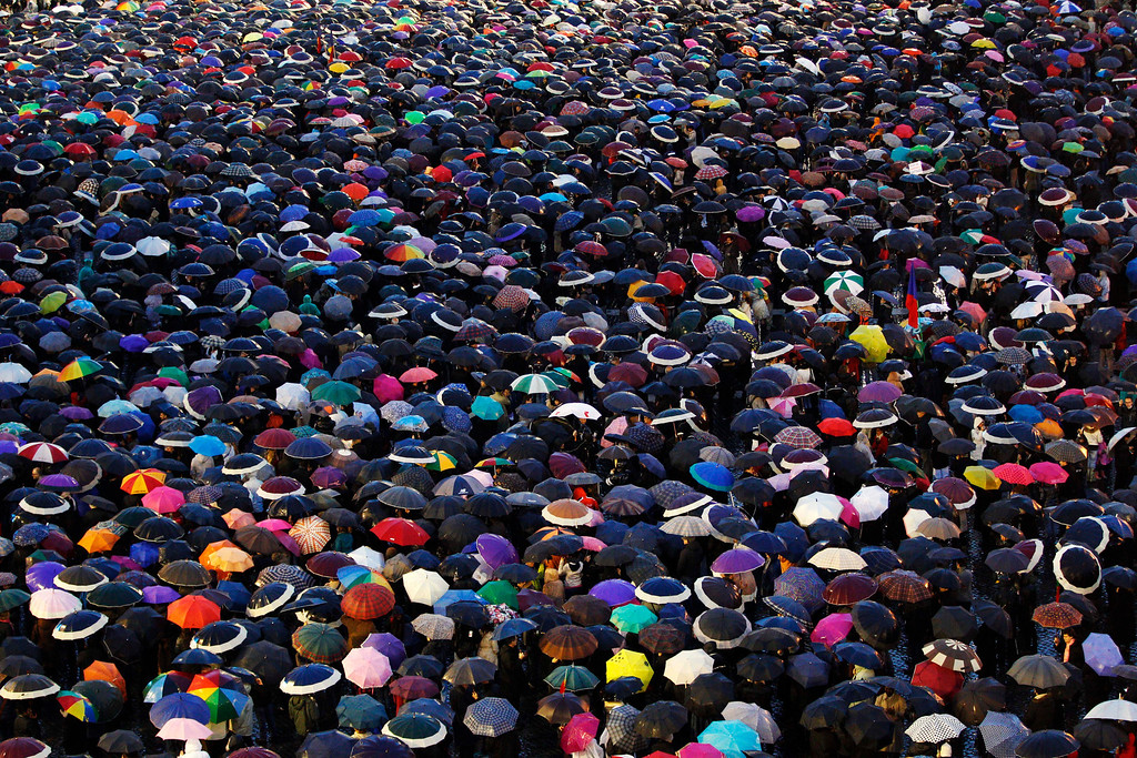 . Visitors cover St. Peter\'s Square with their umbrellas as they wait for the election of a new pope by the cardinals in conclave in the Sistine Chapel at the Vatican, Wednesday, March 13, 2013.(AP Photo/Andrew Medichini)