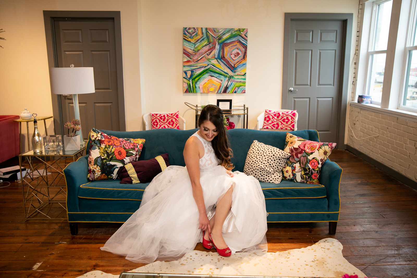 bride slipping into her read wedding heals as she sits on a boho couch surrounded by mid-century furniture and setting