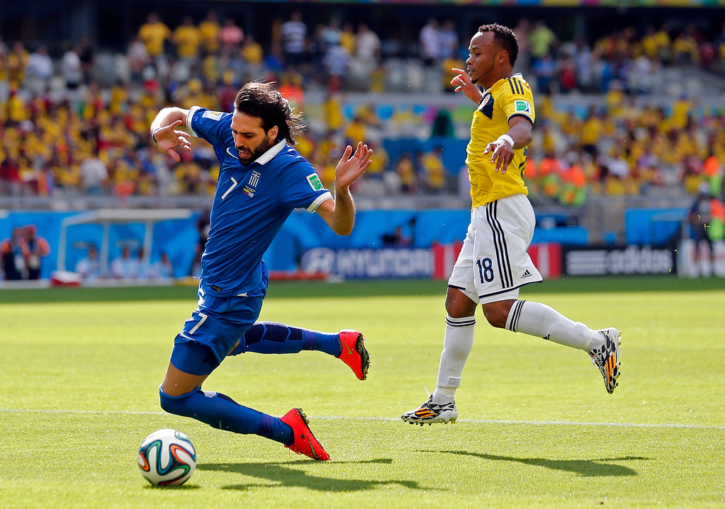 . Greece\'s Giorgos Samaras, left, goes down in the penalty box after a challenge by Colombia\'s Juan Zuniga during the group C World Cup soccer match between Colombia and Greece at the Mineirao Stadium in Belo Horizonte, Brazil, Saturday, June 14, 2014.  No penalty was given. (AP Photo/Jon Super)