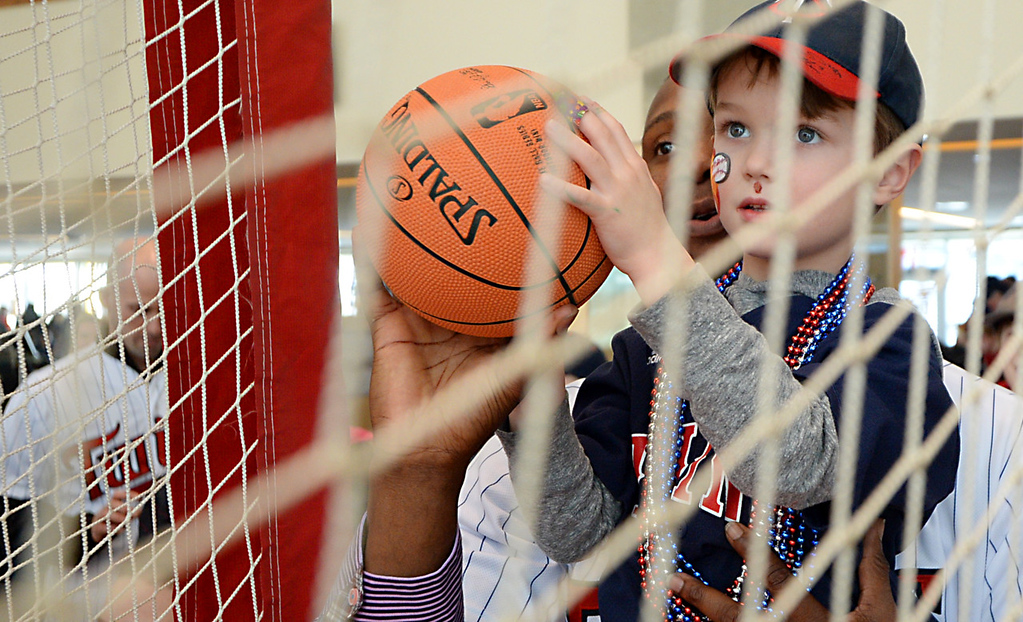 . Samuel Deduno holds up five years-old Logan Steffen as they shoot baskets at Twinsfest at Target Field, Saturday, January 25, 2014(Pioneer Press: John Autey)