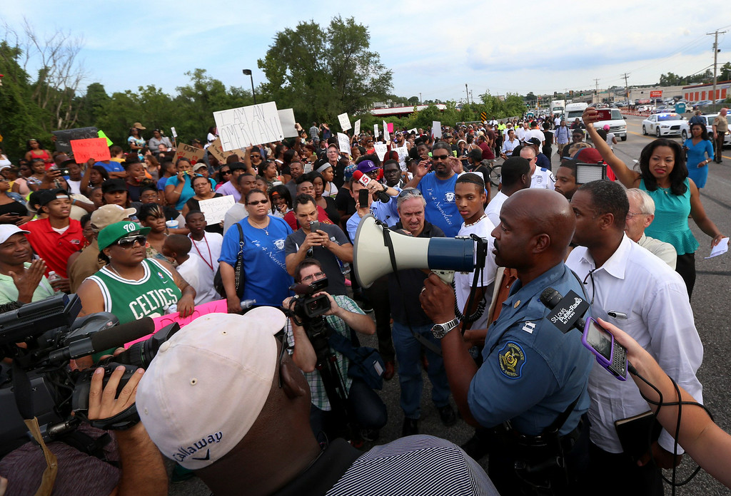 . CHANGES THE WORD SEIZED TO TOOK - Missouri State Highway Patrol Capt. Ronald Johnson addresses the crowd of protesters, asking them to stay on the sidewalk and not block traffic Thursday, Aug. 14, 2014, in Ferguson, Mo. The Missouri Highway Patrol seized took of a St. Louis suburb Thursday, stripping local police of their law-enforcement authority after four days of clashes between officers in riot gear and furious crowds protesting the death of an unarmed black teen shot by an officer. (AP Photo/St. Louis Post-Dispatch, David Carson)