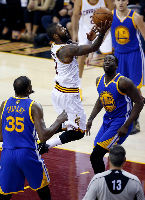 . Cleveland Cavaliers guard Kyrie Irving (2) drives on Golden State Warriors\' Draymond Green (23) and Kevin Durant (35) during the first half of Game 3 of basketball\'s NBA Finals in Cleveland, Wednesday, June 7, 2017. (AP Photo/Ron Schwane)
