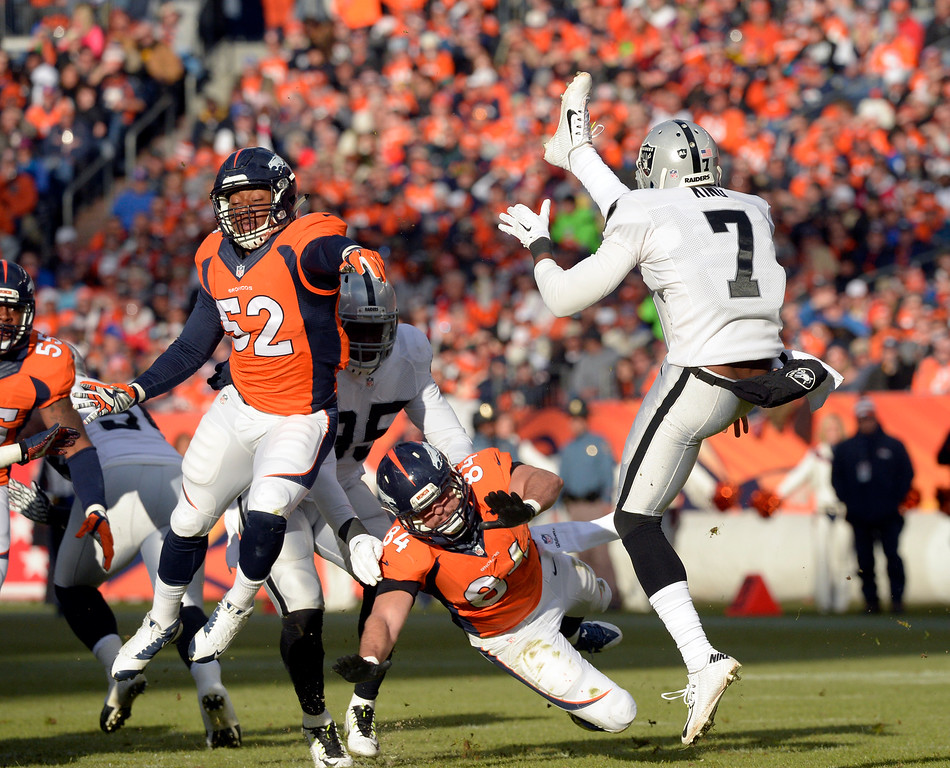 . DENVER, CO - DECEMBER 28: Marquette King (7) of the Oakland Raiders gets the punt off under pressure during the first quarter.  The Denver Broncos played the Oakland Raiders at Sports Authority Field at Mile High in Denver on December, 28 2014. (Photo by Joe Amon/The Denver Post)