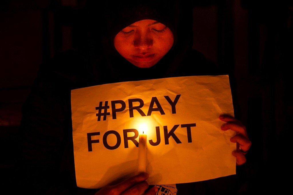 """. An Indonesian Muslim woman holds a placard during a candlelit protest in Surabaya, Eastern Java island on January 14, 2016, to condemn the blasts and gunfire that rocked Jakarta earlier in the day. A \""""Paris-style\"""" suicide strike on the Indonesian capital on January 14 confirmed Southeast Asian governments worst fears -- that citizens returning from fighting alongside the Islamic State group in the Middle East could launch attacks at home. AFP PHOTO /  AFP / JUNI KRISWANTO/AFP/Getty Images"""