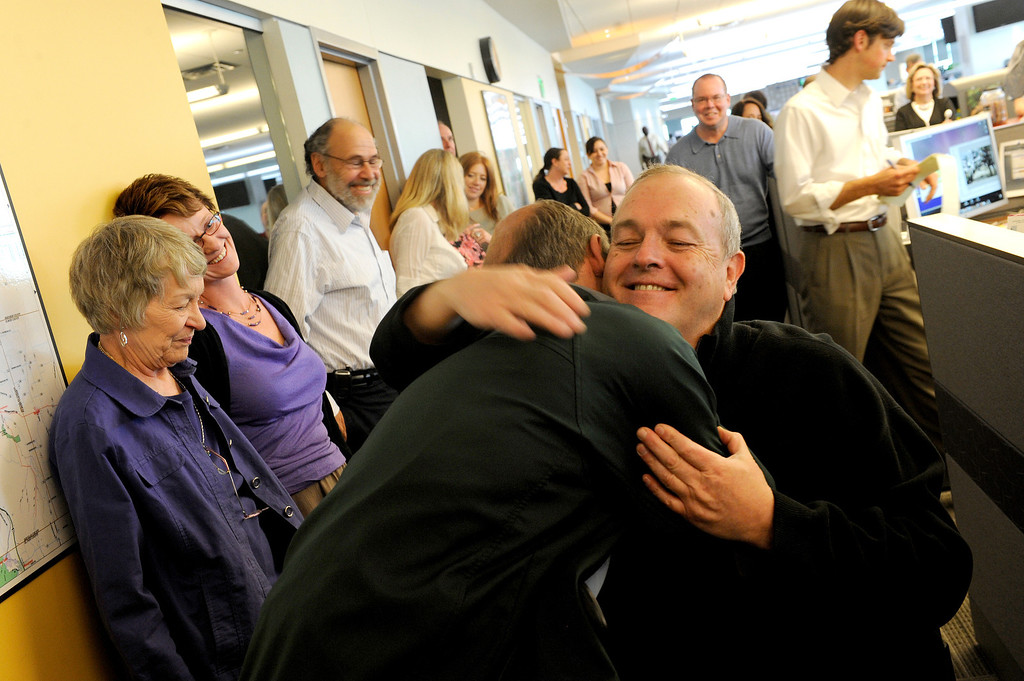 . Craig Walker hugs Dean Singleton, the owner of the Denver Post, after winning the Pulitzer Prize April 12, 2010 for Feature Photography 2010 for his project, Ian Fisher, An American Soldier.   Judy DeHaas, The Denver Post