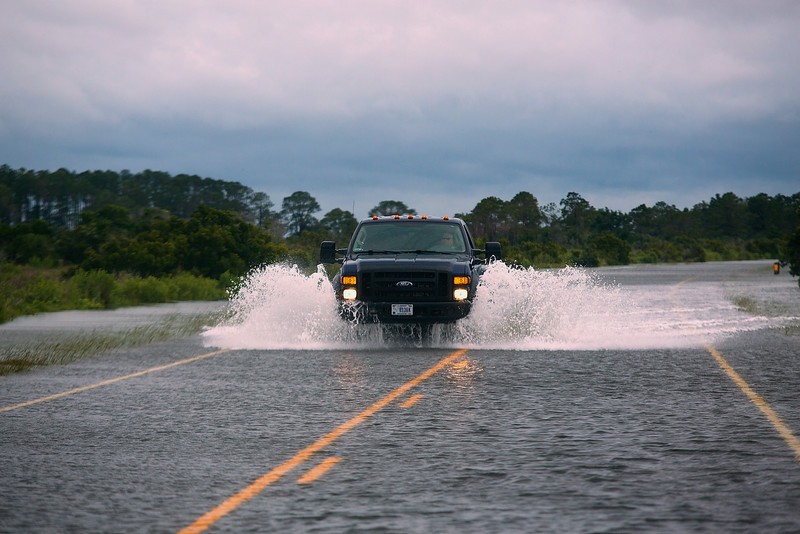 . A motorist drives through flooded North Carolina Highway 12 as the wind from the Hurricane Arthur pushes sound water in, south of Nags Head, N.C., Friday, July 4, 2014. Arthur struck North Carolina as a Category 2 storm with winds of 100 mph late Thursday, taking about five hours to move across the far eastern part of the state. (AP Photo/The Virginian-Pilot, Hyunsoo Leo Kim)