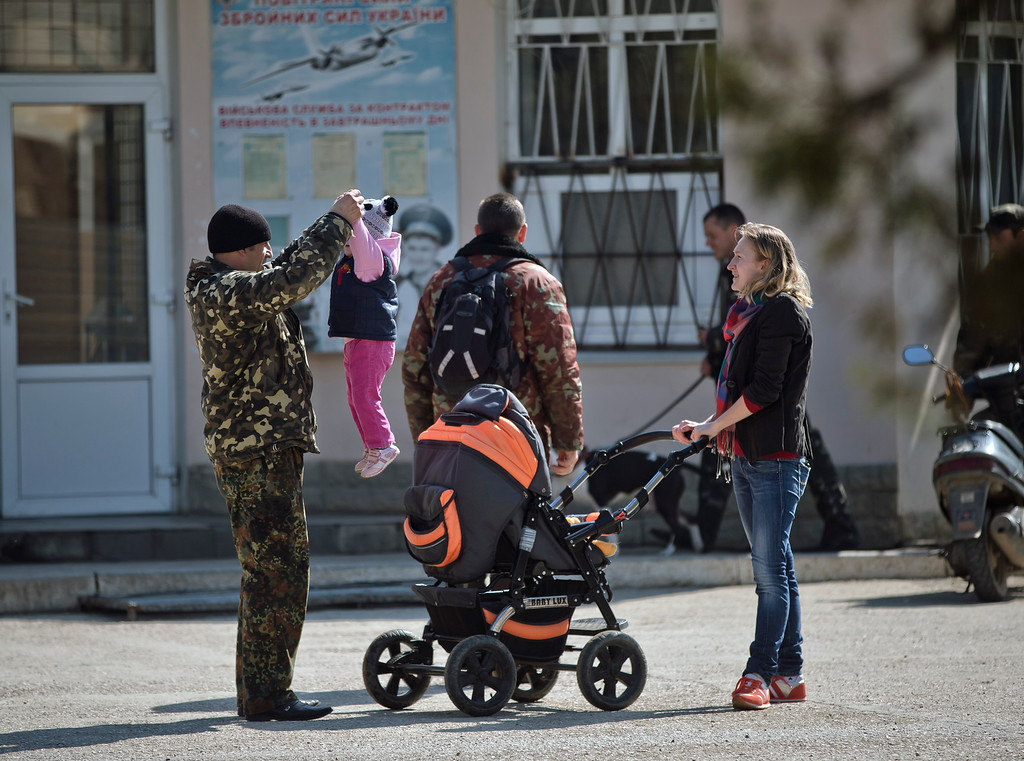 . A Ukrainian airman plays with a child at the Belbek air base, outside Sevastopol, Crimea, Friday, March 21, 2014. The base commander Col. Yuliy Mamchur said he was asked but the Russian military to turn over the base but is unwilling to do so until he receives orders from the Ukrainian defense ministry. (AP Photo/Vadim Ghirda)