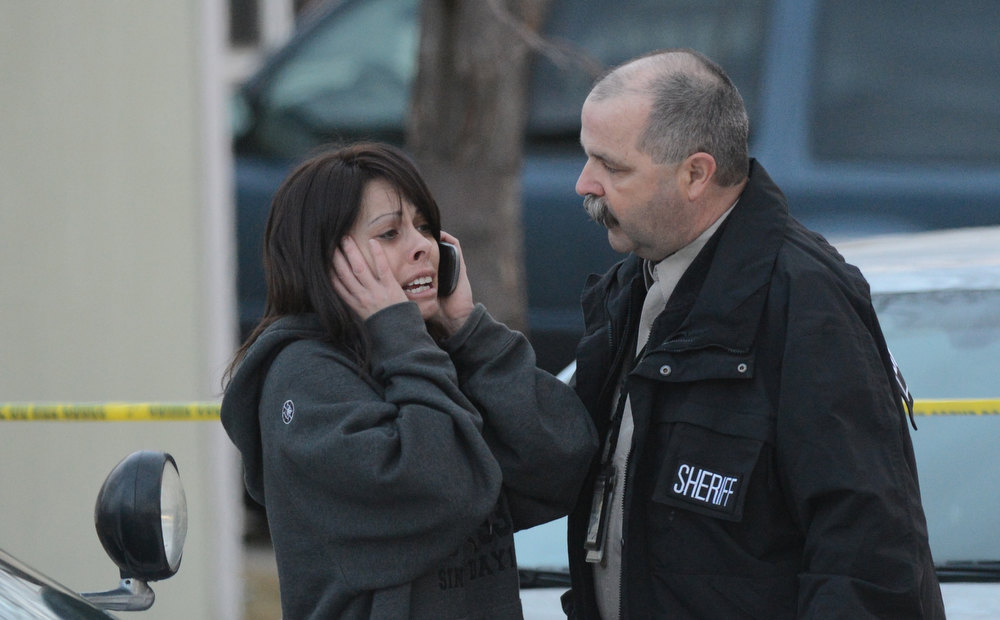 . A Weld County Sheriff Officer conforts a women, Tuesday, December 18, 2012, outside a home where four people were found dead in Longmont. RJ Sangosti, The Denver Post