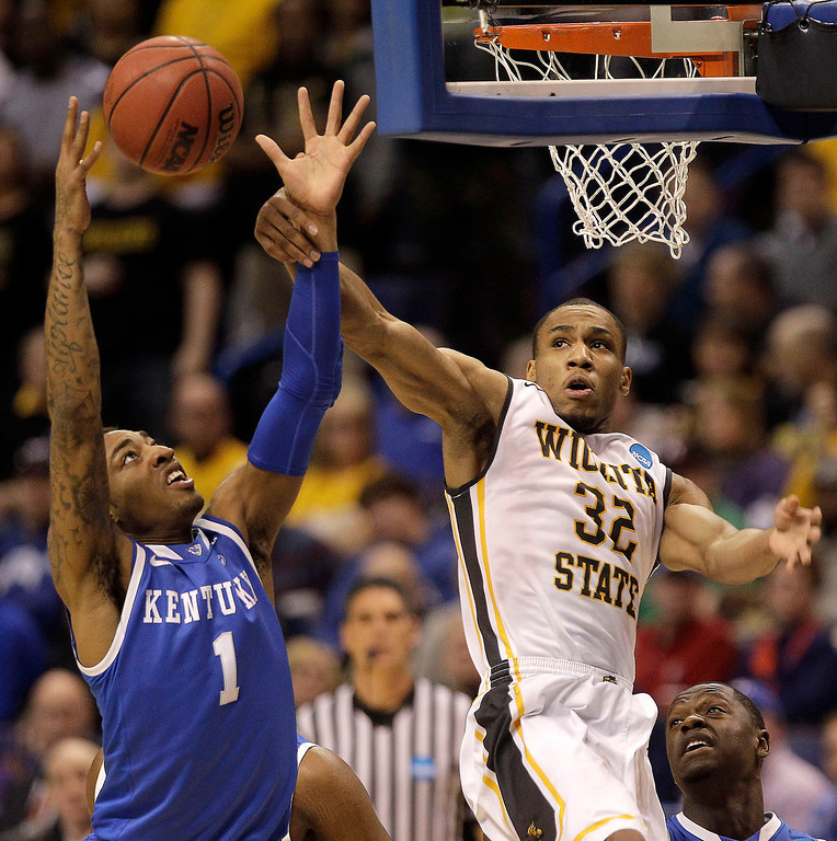 . Wichita State\'s Tekele Cotton (32) and Kentucky\'s James Young (1) battle for a rebound during the first half of a third-round game at the NCAA college basketball tournament Sunday, March 23, 2014, in St. Louis. (AP Photo/Charlie Riedel)