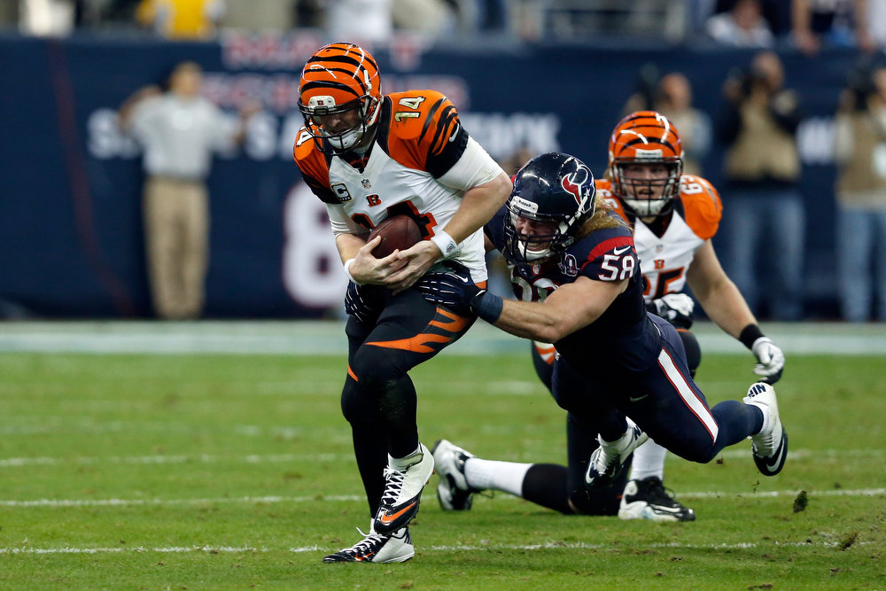 Description of . Andy Dalton #14 of the Cincinnati Bengals runs with the ball against Brooks Reed #58 of the Houston Texans during their AFC Wild Card Playoff Game at Reliant Stadium on January 5, 2013 in Houston, Texas.  (Photo by Scott Halleran/Getty Images)