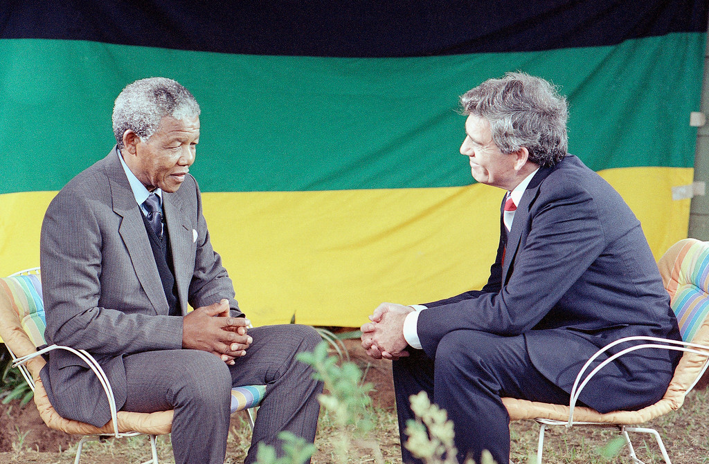 . CBS anchorman Dan Rather, right, and Nelson Mandela Mandela spoke during one of the first interviews Mandela has given since his release last Sunday, after serving 27 years in prison. During the interview at Mandela\'s Soweto home, Wednesday, Feb. 14, 1990, the African National Congress leader spoke about his years in jail. At rear is the ANC flag. (AP Photo/ John Parkin)