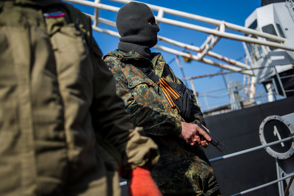 . A man in an unmarked uniform with a ribbon symbolizing the Soviet victory in WWII, holds a gun during seizure of the Ukrainian corvette Khmelnitsky in Sevastopol, Crimea, Thursday, March 20, 2014.   (AP Photo/Andrew Lubimov)