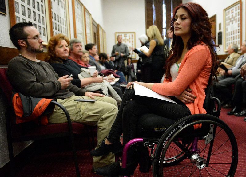 . Karina Vargas, right, who was paralyzed from a shooting outside Aurora Central High School, waits to testify before Colorado lawmakers at the Colorado State Capitol, March, 04, 2013. Vargas is in support of stronger gun laws in Colorado. (Photo By RJ Sangosti/The Denver Post)