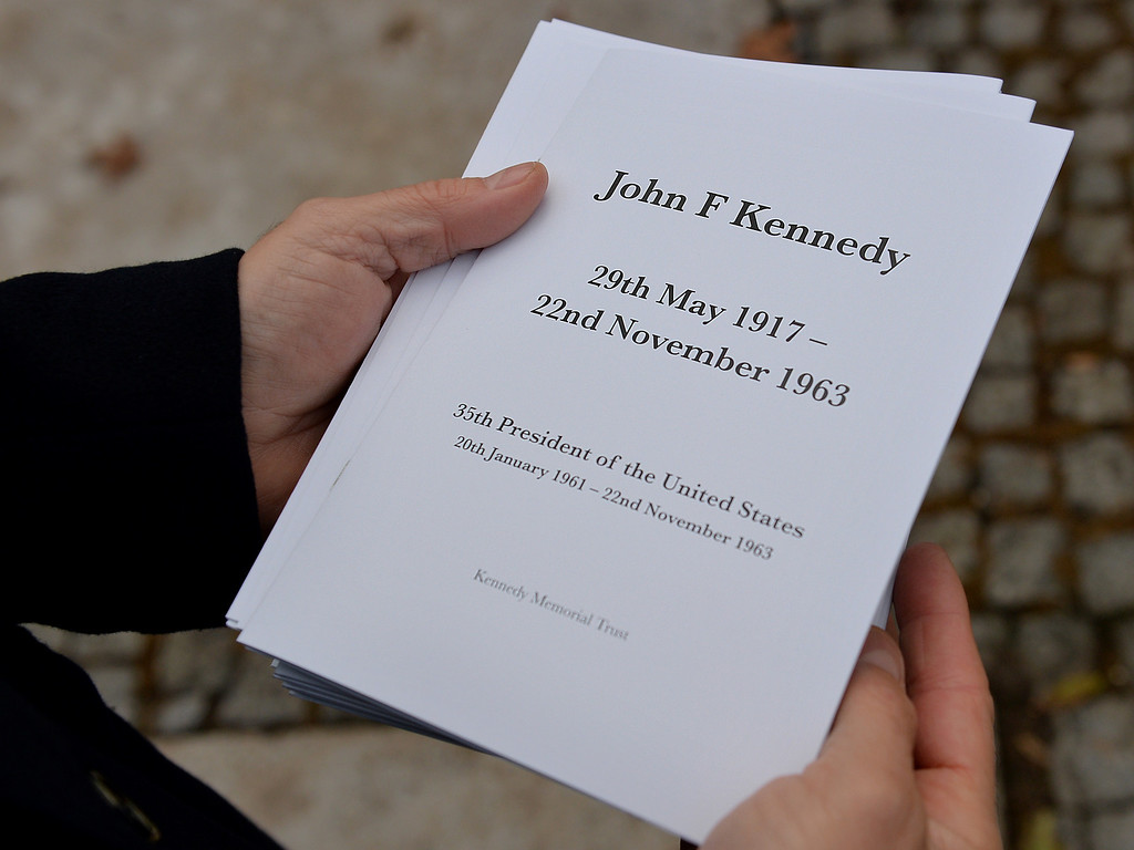 . An attendee holds an order of service at a memorial for former US President John F Kennedy in Runnymede, Surrey on November 22, 2013, to mark the 50th anniversary of his assassination. AFP PHOTO / BEN  STANSALL/AFP/Getty Images