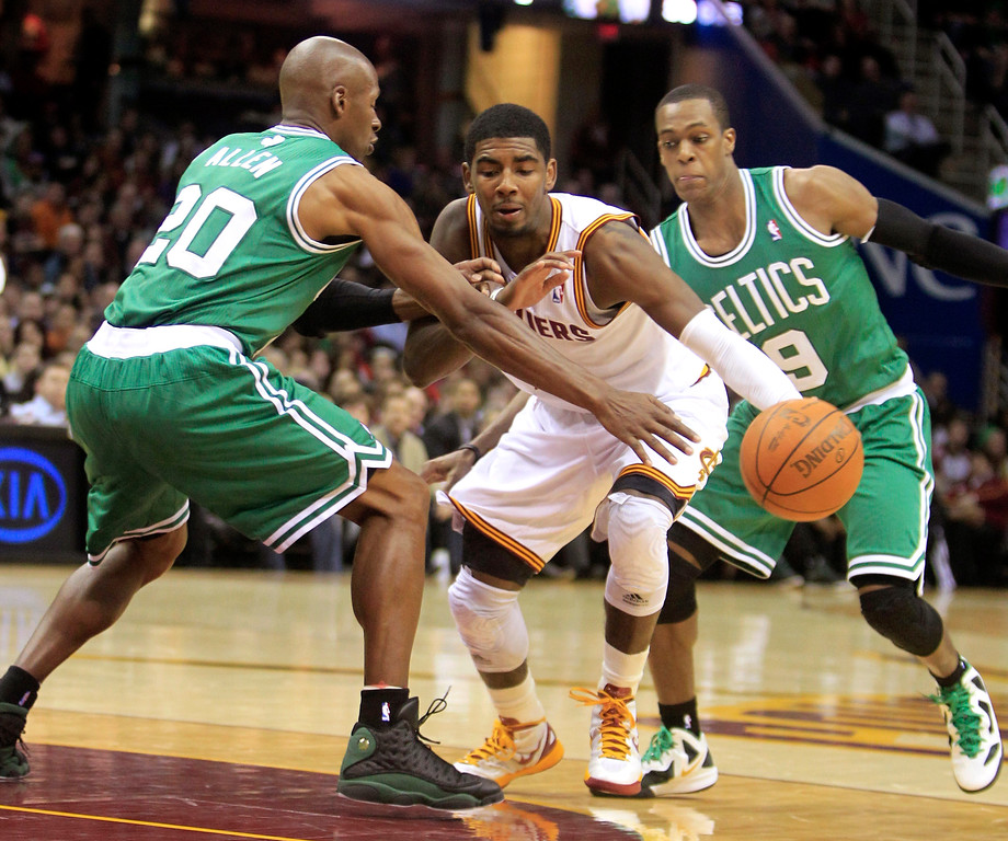 . Cleveland Cavaliers\' Kyrie Irving (2) drives between Boston Celtics\' Ray Allen (20) and Rajon Rondo (9) in the second quarter of an NBA basketball game, Tuesday, Feb. 28, 2012, in Cleveland. (AP Photo/Tony Dejak)
