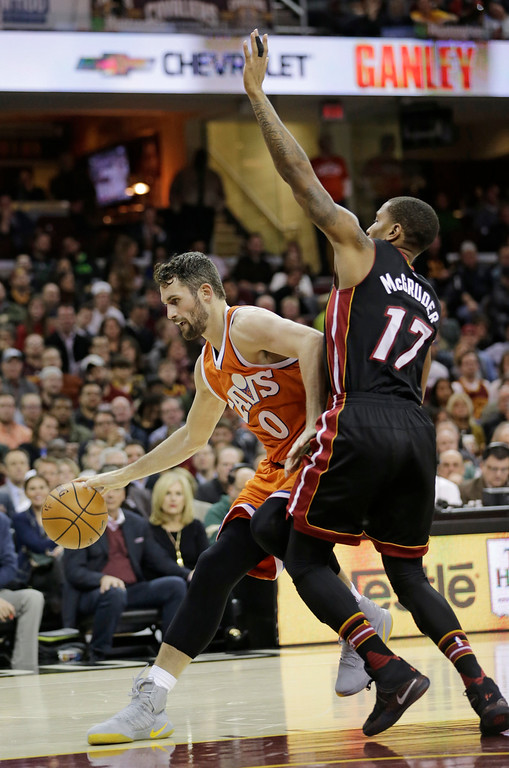 . Cleveland Cavaliers\' Kevin Love (0) drives past Miami Heat\'s Rodney McGruder (17) in the first half of an NBA basketball game Friday, Dec. 9, 2016, in Cleveland. The Cavaliers won 114-84. (AP Photo/Tony Dejak)