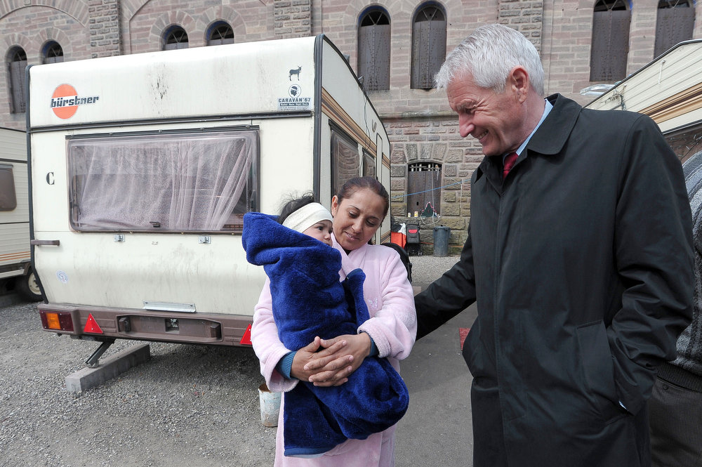 . Council of Europe Secretary General Thorbjoern Jagland (R) speaks with a woman  of the Roma community holding her child as he visits a camp as part of the International Roma Day on April 8, 2013 in Strasbourg, eastern France.       FREDERICK FLORIN/AFP/Getty Images