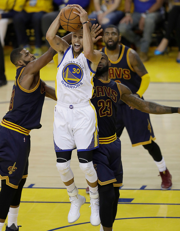. Golden State Warriors guard Stephen Curry (30) grabs the ball in front of Cleveland Cavaliers center Tristan Thompson, left, forward LeBron James (23) and guard Kyrie Irving, rear, during the first half of Game 1 of basketball\'s NBA Finals in Oakland, Calif., Thursday, June 1, 2017. (AP Photo/Marcio Jose Sanchez)