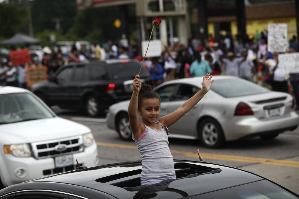 . A young girl protesting Michael Brown\'s murder is seen in a vehicle with her hands in the air August 17, 2014 in Ferguson, Missouri.Tensions still run high in the Ferguson community after 18 -year-old Michael Brown was killed by a Ferguson Police Officer August 9 on Canfield Drive. (Photo by Joshua Lott/Getty Images)