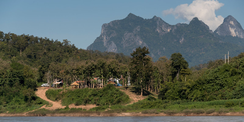 Shoreline village with rocky mountains in background, River Mekong, Pak Ou District, Luang Prabang, Laos