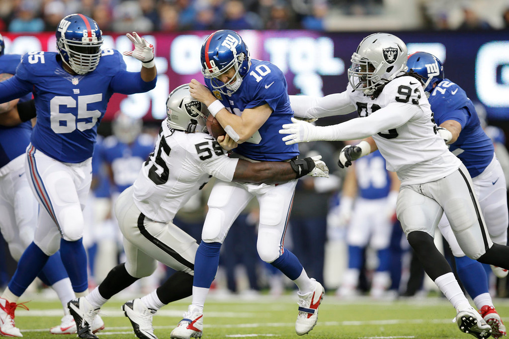 . New York Giants quarterback Eli Manning (10) is sacked by Oakland Raiders outside linebacker Sio Moore (55) and defensive end Jason Hunter (93) during the first half of an NFL football game on Sunday, Nov. 10, 2013, in East Rutherford, N.J. (AP Photo/Kathy Willens)