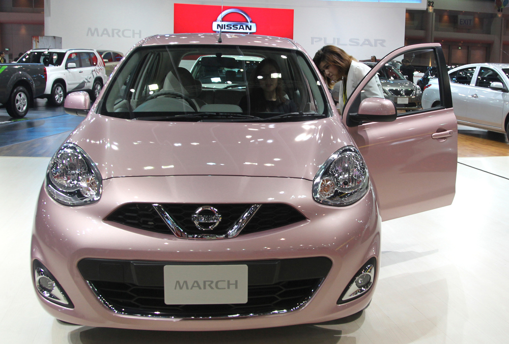 . Thai visitors inspect a face-lifted Nissan March subcompact, also called Nissan Micra, on the press day of the Bangkok Motor Show in Bangkok, Thailand, Tuesday, March 26, 2013. The 34th running of the auto show is opened to the public from Wednesday. (AP Photo/Sakchai Lalit)