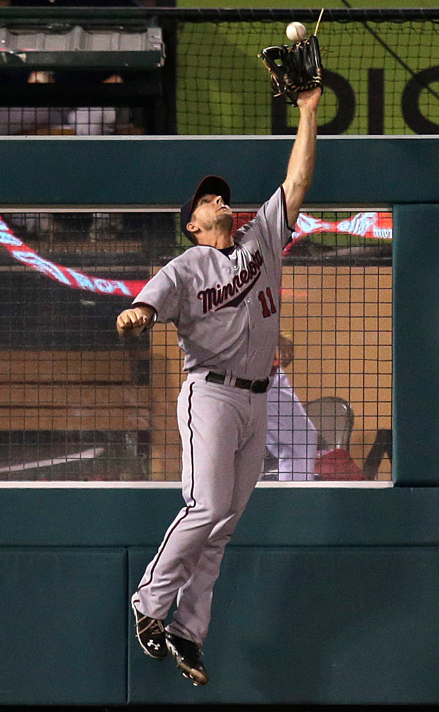 . Minnesota Twins left fielder Clete Thomas jumps over the fence to catch a ball hit by Los Angeles Angels\' Chris Iannetta during the eighth inning of a baseball game on Monday, July 22, 2013, in Anaheim, Calif. (AP Photo/Jae C. Hong)