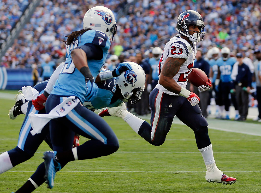 . Houston Texans running back Arian Foster (23) scores a touchdown on a 2-yard run as Tennessee Titan defenders Michael Griffin (33) and Akeem Ayers, center, pursue him in the second quarter of an NFL football game on Sunday, Dec. 2, 2012, in Nashville, Tenn. (AP Photo/Joe Howell)
