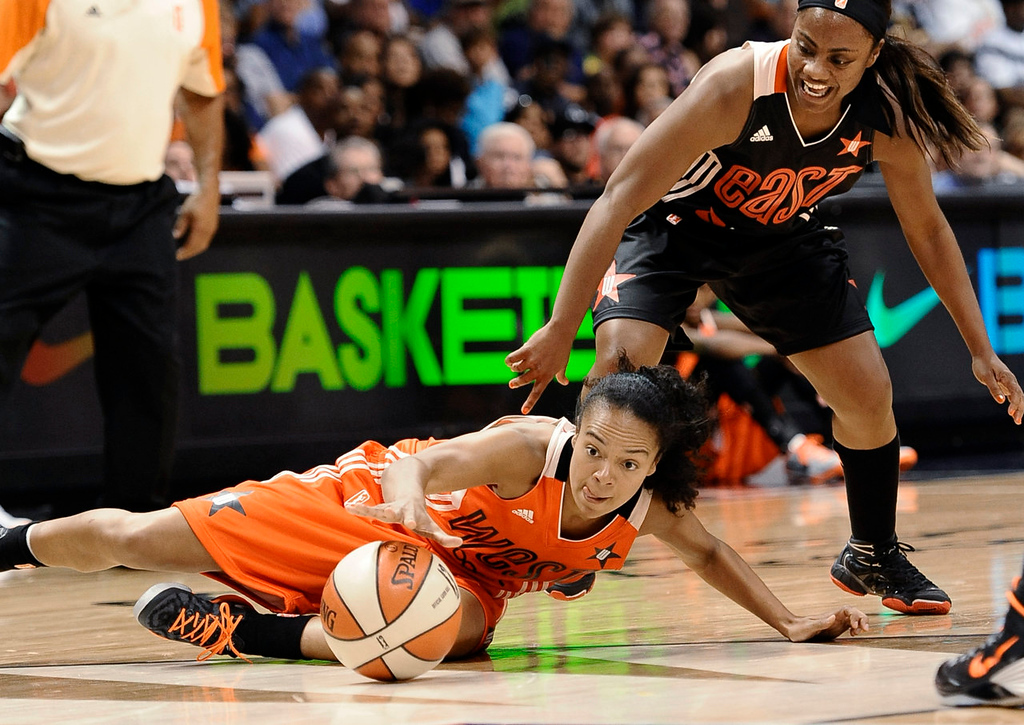 . West\'s Kristi Toliver, left, of the Los Angeles Sparks, and East\'s Ivory Latta, of the Washington Mystics, chase a loose ball during the second half. (AP Photo/Jessica Hill)
