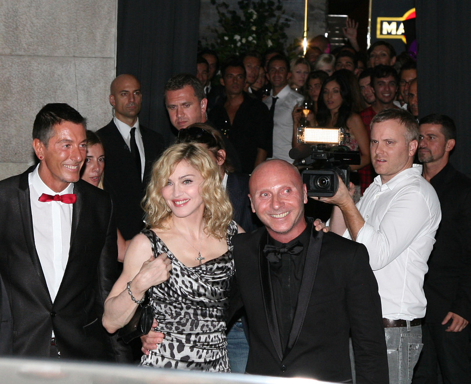 """. U.S singer Madonna between Italian stylists Stefano Gabbana, left, and Domenico Dolce, right, at the entrance of their \""""Gold\"""" restaurant in Milan where she attended a party after her concert, part of her Sticky and Sweet tour, at the San Siro stadium in Milan, Italy, Tuesday night, July 14, 2009. (AP Photo/Tommaso Balestra)"""