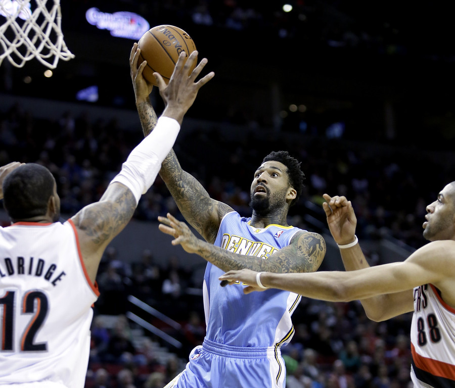 . Denver Nuggets forward Wilson Chandler, center, goes to the hoop against Portland Trail Blazers\' LaMarcus Aldridge, left, and Nicolas Batum, from France, during the first half of an NBA basketball game in Portland, Ore., Saturday, March 1, 2014. (AP Photo/Don Ryan)