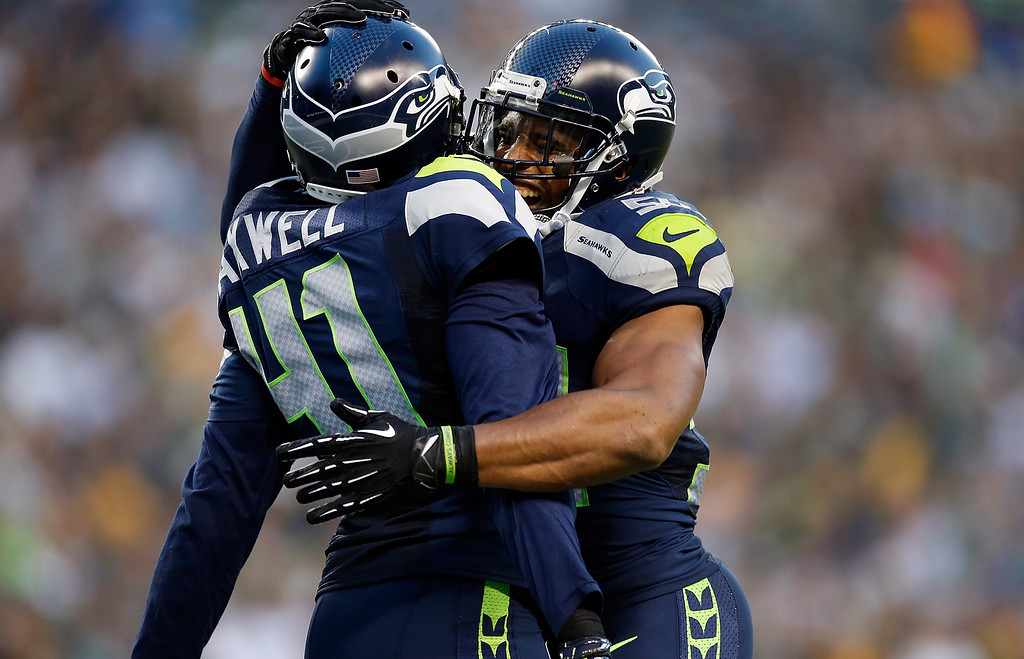 . SEATTLE, WA - SEPTEMBER 04: Cornerback Byron Maxwell #41 and linebacker Bobby Wagner #54 of the Seattle Seahawks celebrate after Maxwell intercepted a pass during the third quarter of the game against the Green Bay Packers at CenturyLink Field on September 4, 2014 in Seattle, Washington.  (Photo by Otto Greule Jr/Getty Images)