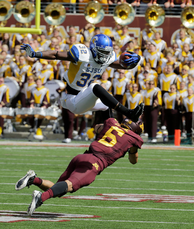 . San Jose State running back Jason Simpson (32) leaps over Minnesota defensive back Grayson Levine (6) during the fourth quarter of an NCAA college football game in Minneapolis Saturday, Sept. 21, 2013. The play was called back after San Jose State guard Nicholas Kaspar earned a 15-yard penalty for a chop block. Minnesota beat San Jose State 43-24. (AP Photo/Ann Heisenfelt)