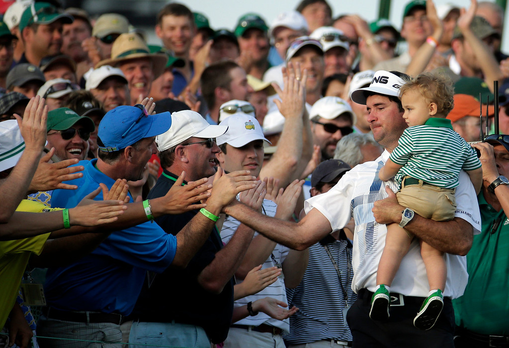 . Bubba Watson, carrying his son Caleb, is congratulated by spectators after winning the Masters golf tournament Sunday, April 13, 2014, in Augusta, Ga. (AP Photo/Charlie Riedel)