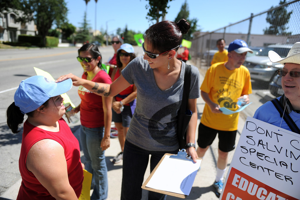 . Jennifer Davis, center, adjusts the cap of Angela Armenta during a picket in front of the office of LAUSD board member Tamar Galatzan in Lake Balboa, Wednesday, July 24, 2013. Parents and Teachers United for Action picketed to voice their opposition to the district�s transitioning of special education students onto regular education campuses.   (Michael Owen Baker/L.A. Daily News)