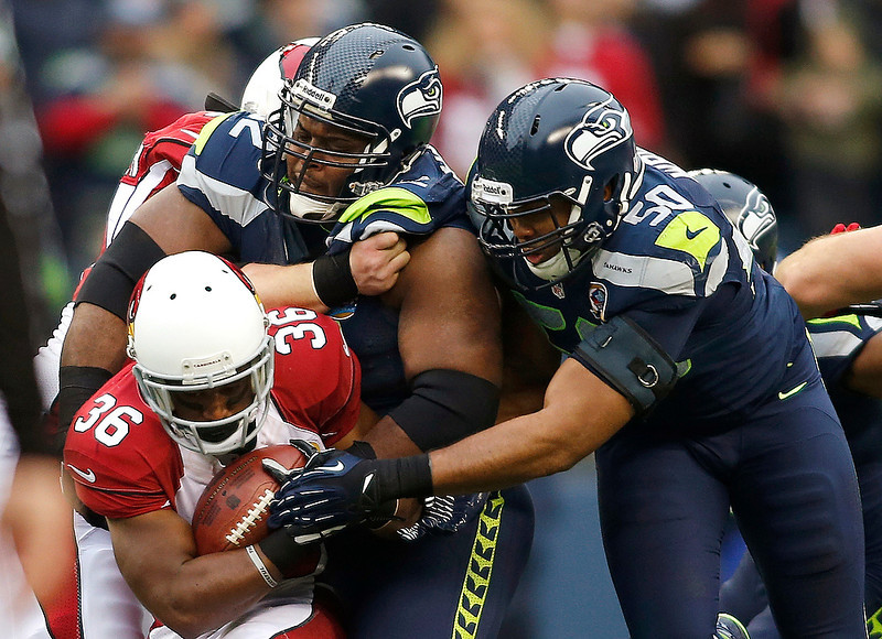 . Seattle Seahawks defensive tackle Brandon Mebane (92) and outside linebacker K.J. Wright (50) tackle Arizona Cardinals running back LaRod Stephens-Howling (36) during the first quarter of an NFL football game in Seattle, Sunday, Dec. 9, 2012. (AP Photo/John Froschauer)