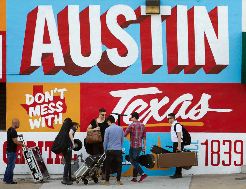 . A band is on the move on the corner of Sixth Street and I-35 at South by Southwest on Thursday March 14, 2013, in Austin, Texas. (AP Photo/Austin American-Statesman, Jay Janner)