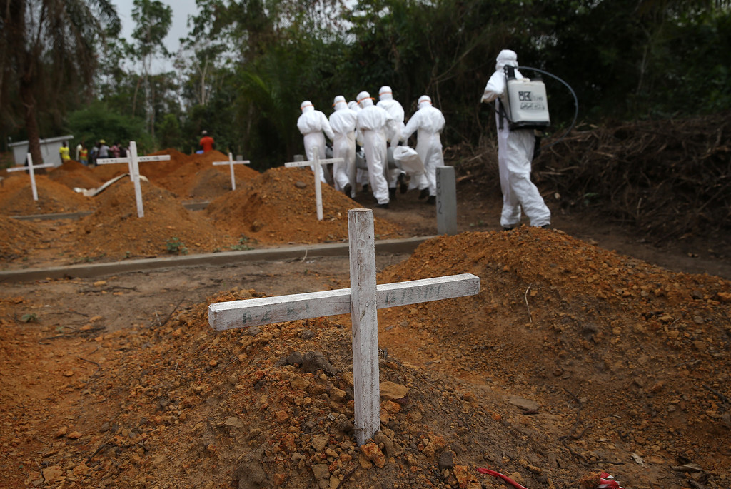 ". A burial team carries a dead body to be interred at the U.S.-built cemetery for ""safe burials\"" on January 27, 2015 in Disco Hill, Liberia.  (Photo by John Moore/Getty Images)"