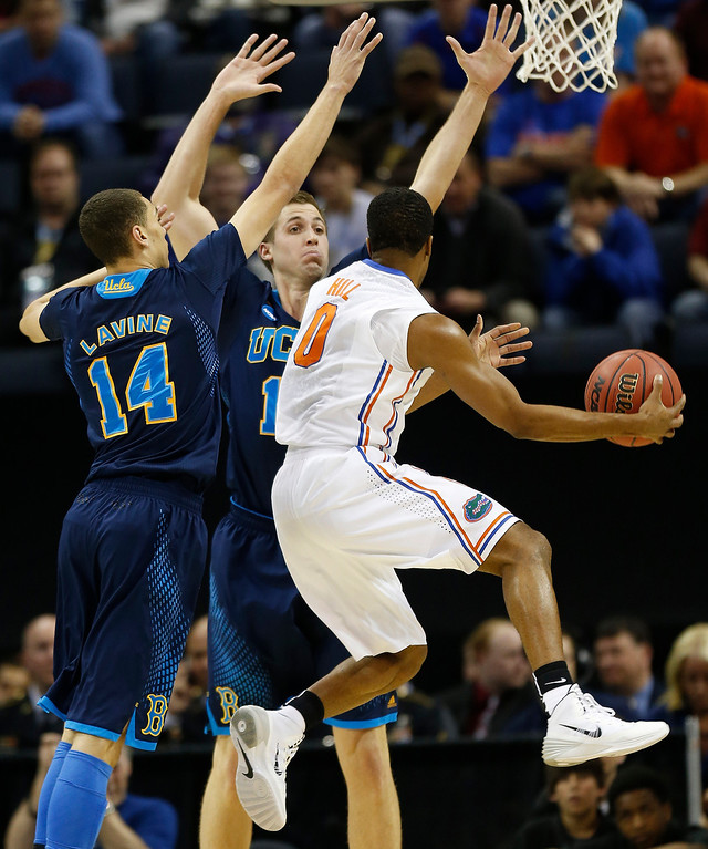 . UCLA\'s Zach LaVine (14) and David Wear (12) defend against Florida Kasey Hill (0) during the first half in a regional semifinal game at the NCAA college basketball tournament, Thursday, March 27, 2014, in Memphis, Tenn. (AP Photo/John Bazemore)