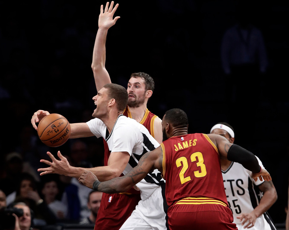 . Brooklyn Nets\' Brook Lopez, front left, drives past Cleveland Cavaliers\' Kevin Love, center, and LeBron James, right, during the first half of an NBA basketball game Friday, Jan. 6, 2017, in New York. (AP Photo/Frank Franklin II)