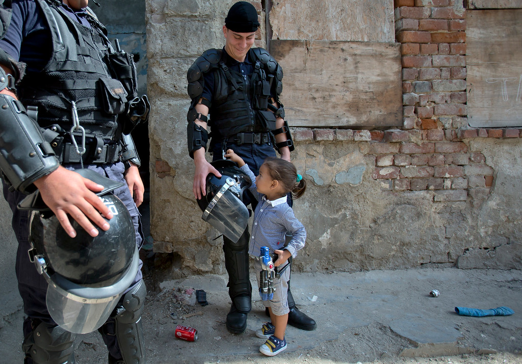 . A Roma child touches a riot policeman\'s equipment during the eviction of more than 100 people from the homes they lived, in Bucharest, Romania, Monday, Sept. 15, 2014. (AP Photo/Vadim Ghirda)