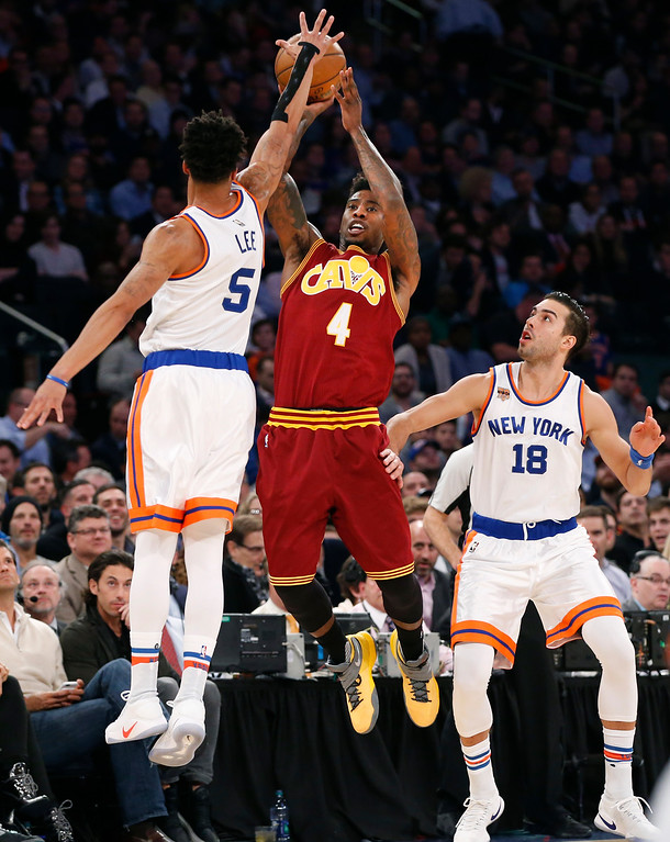 . New York Knicks guard Courtney Lee (5) defends as Cleveland Cavaliers guard Iman Shumpert (4) shoots a three-point shot with New York Knicks guard Sasha Vujacic (18) looking on from the floor in the first quarter of an NBA basketball game at Madison Square Garden in New York, Wednesday, Dec. 7, 2016. (AP Photo/Kathy Willens)