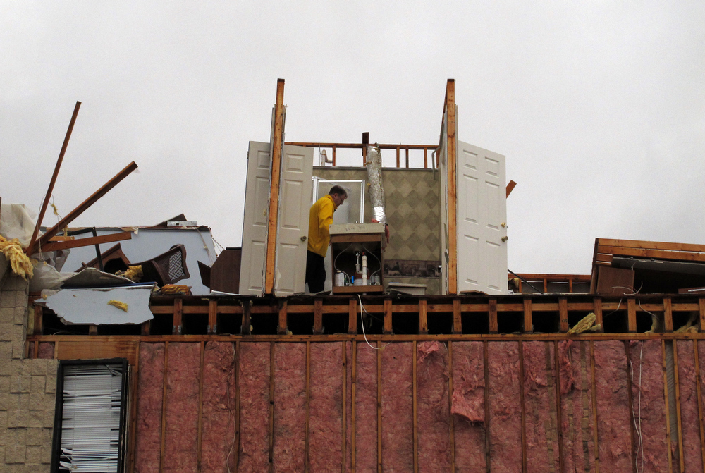 Description of . A man inspects damage to the third floor of a building in Mount Juliet, Tenn., that was severely damaged in a severe storm on Wednesday, Jan. 30, 2013.  Forecasters examined the damage path of 4.6 miles Wednesday morning and estimated the peak wind speed at 115 mph, qualifying the tornado as an EF-2 twister. The path of damage was about 150 yards wide. (AP Photo/Kristin M. Hall)